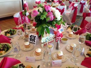 """The room was decorated in high fashion with beauty and elegance. The stunning table decorations paled in comparison to the hearts of sisterhood joined together in High Point, NC for their Annual Pink Ribbon Luncheon. These are my people and as a humorist speaker I would speak to every single Pink Ribbon group across the world if I could. At the end of the luncheon themed after my funny book for women, """"Bury me with My Pearls"""" I decided to tie a pink ribbon for breast cancer awareness around my heart."""